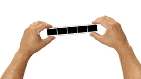 Hands Holding a Strip of Film. A filmstirp is held by two hands for your images on white royalty free stock images