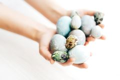 Hands holding stylish Easter eggs on white wooden background. Modern colorful easter eggs painted with pastel natural dye in. Marble colors. Happy Easter stock photo
