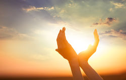 Hands holding the sun. At dawn.  Photo with clouds on background Stock Image