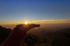 Hands holding the sun at sunrise Royalty Free Stock Photos