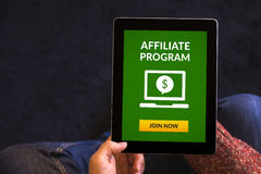 Hands holding tablet with affiliate program concept on screen. Hands holding digital tablet computer with affiliate program concept on screen. All screen content Stock Image