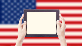 Hands holding tablet on blurred USA Flag with clipping path inside royalty free stock photo