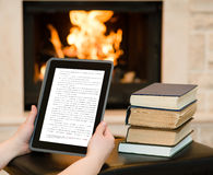 Hands holding tablet computer near the fireplace Stock Image