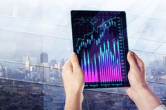 Economy and stock concept. Hands holding tablet with forex chart on abstract city background. Economy and stock concept. Double exposure Royalty Free Stock Photography