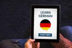 Hands holding tablet with learn german concept on screen Stock Photo