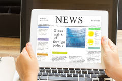 Hands holding tablet with news site. Someones hands holding tablet with news site Royalty Free Stock Photography