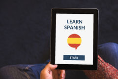 Hands holding tablet with online learn spanish concept on screen Royalty Free Stock Photo