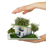 Hands holding tablet pc and small house with land Royalty Free Stock Photo