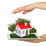 Hands holding tablet pc and small house with land Royalty Free Stock Photography