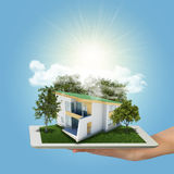 Hands holding tablet pc and small house with land Royalty Free Stock Photos