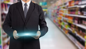 Hands holding tablet pc in supermarket in blurry Royalty Free Stock Images
