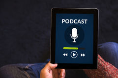 Hands holding tablet with podcast concept on screen Stock Photography