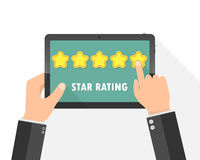 Hands holding a tablet with rating stars. Vector illustration Stock Images