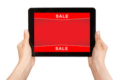 Hands holding a tablet with sale on a red screen Royalty Free Stock Photo