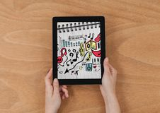 Hands holding tablet showing music doodles on sketchbook Royalty Free Stock Image