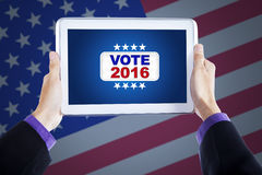 Hands holding tablet with vote button Stock Photography