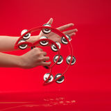Hands holding tambourine on red background Stock Photo