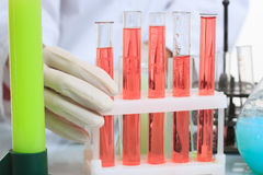 Hands holding test tubes with chemical elements Royalty Free Stock Image