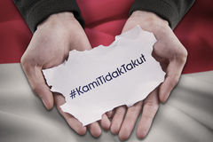 Hands holding text of Kami Tidak Takut Stock Images