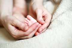 Hands holding tiny foot of newborn baby Royalty Free Stock Images