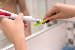 Hands holding a toothbrush and placing toothpaste on it. In front of mirror in the modern tiled bathroom Stock Photos