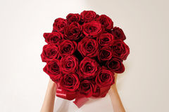 Hands holding top view of luxury bouquet of red roses top view w. Ith red bow. On Valentine's day holiday royalty free stock images