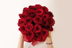 Hands holding top view of luxury bouquet of red roses top view w. Ith red bow. On Valentine's day holiday stock photo