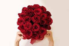 Hands holding top view of luxury bouquet of red roses top view w. Ith red bow. On Valentine's day holiday stock photography
