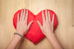 Hands holding toy red heart on wooden surface Stock Photography
