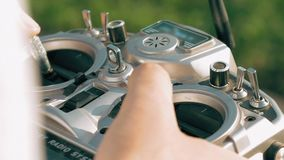 Hands holding a transmitter controlling FPV drone stock footage