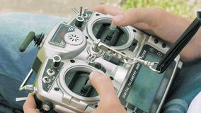 Hands holding a transmitter controlling FPV drone stock video footage