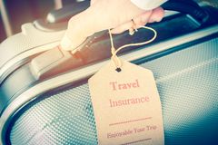 Hands holding Travel Insurance tag on Suitcase safety with lette. Rs enjoyable your trip on bag light blurred background, that is intended cover medical expenses Royalty Free Stock Image