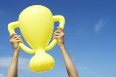 Hands Holding Trophy Bright Blue Sky. Hands of winning champion holding inflatable yellow trophy in bright blue sky Stock Photo