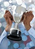Hands holding trophy cup with sparkling light bokeh background. Digital composite of Hands holding trophy cup with sparkling light bokeh background Royalty Free Stock Images