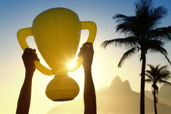 Hands Holding Trophy Rio de Janeiro Skyline. Hands holding inflatable trophy above sunset skyline of Rio de Janeiro Brazil Stock Image