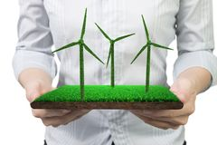 Hands holding turf tile with grass texture of wind turbines stock photos