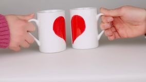 Hands holding two coffee cups painted with halves red heart shape and put near to make one heart. Hands of young couple holding two coffee cups painted with stock video footage