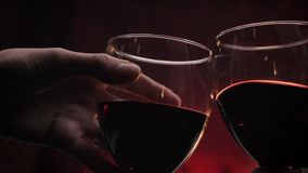 Hands holding two glasses of red wine during date, romantic dark red background, high quality video.  stock footage
