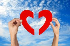 Hands holding two half of heart shape with blue sky Royalty Free Stock Images
