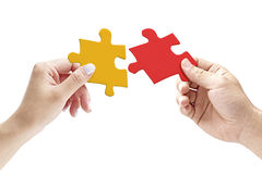 Hands holding two matching jigsaw pieces. Hands of a male and female putting together two matching jigsaw pieces, isolated on white background royalty free stock images