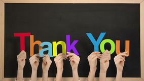 Hands holding up thank you. Against chalkboard stock footage