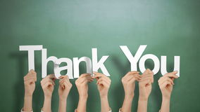 Hands holding up thank you. Against chalkboard stock video