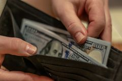 Hands holding us dollar bills and small money pouch stock photo