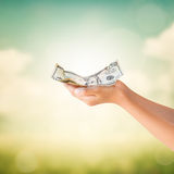 Hands holding US Dollars note with natural background Royalty Free Stock Photography
