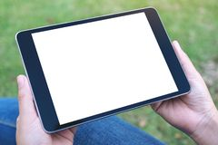 Hands holding and using black tablet pc with blank white desktop screen while writing on notebooks in office. Mockup image of hands holding and using black stock photo