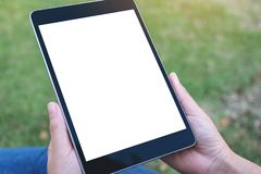 Hands holding and using black tablet pc with blank white desktop screen while writing on notebooks in office. Mockup image of hands holding and using black stock images
