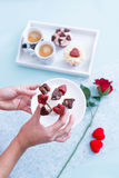 Hands holding Valentines cupcake on saucer Royalty Free Stock Image