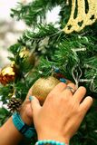 Hands holding of various decorations on the Christmas tree. Royalty Free Stock Photos