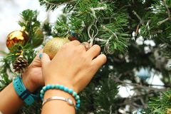 Hands holding of various decorations on the Christmas tree. Stock Image