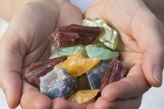 Hands holding various pieces of calcite stock image